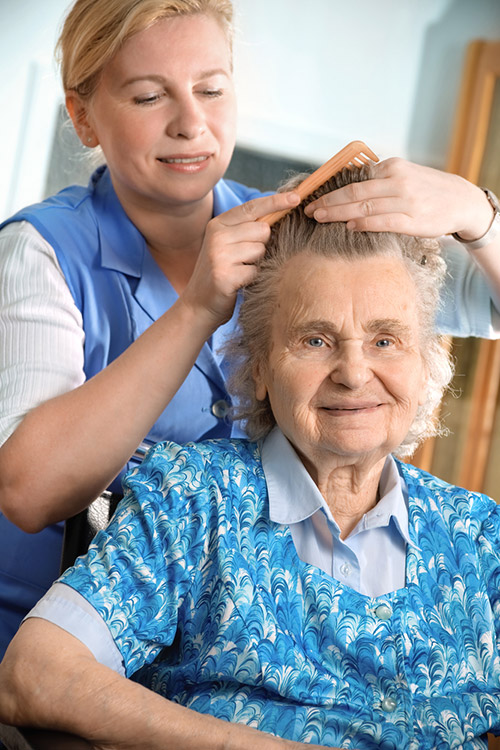 Elderly woman having her hair brushed by a Provider
